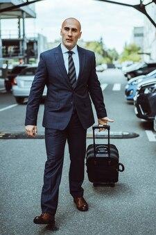 Homme d'affaires en costume sur un parking transportant une valise à travers des voitures garées. homme d'affaires en
