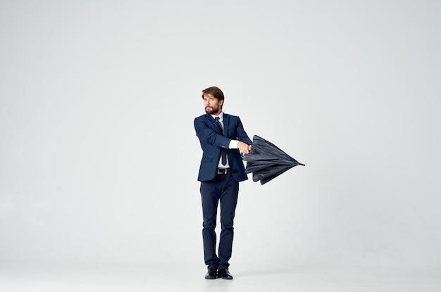 Homme d'affaires en costume posant sur un fond clair avec un parapluie noir à la main
