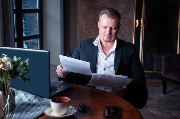 Homme d'affaires en costume regarde à travers les papiers à l'intérieur chic de la salle