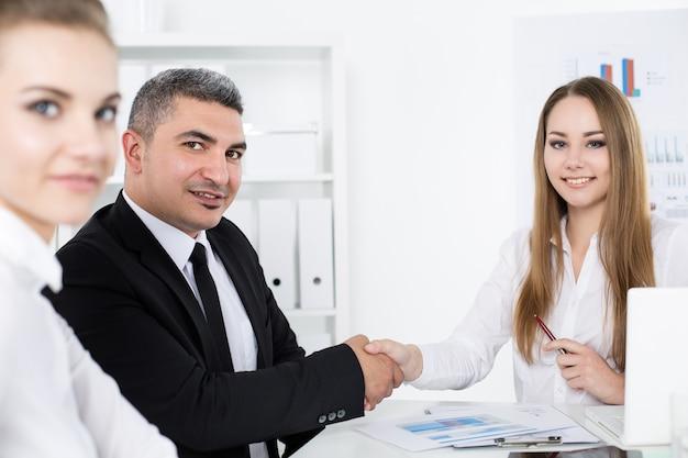 Homme d'affaires en costume, serrant la main de la jeune femme d'affaires. les partenaires ont conclu un accord et l'ont scellé avec un fermoir. geste de salutation formel