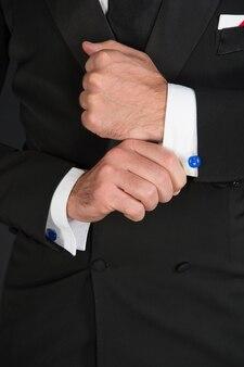 Homme d'affaires en costume de smoking noir et chemise blanche et cravate noire sur fond noir. sans visage. l'homme d'affaires dans le noir. prise de vue en studio