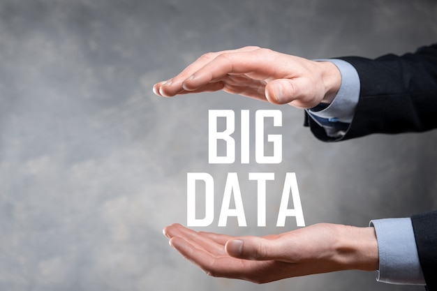 Homme d'affaires en costume sur une surface sombre détient l'inscription big data
