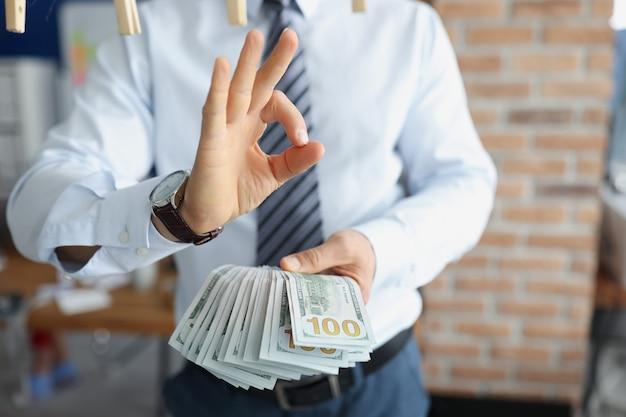 Homme d'affaires en costume tenant beaucoup de billets d'un dollar dans ses mains et montrant un geste ok en gros plan