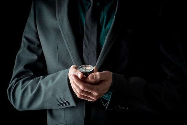 Homme d'affaires en costume tenant la boussole dans ses mains