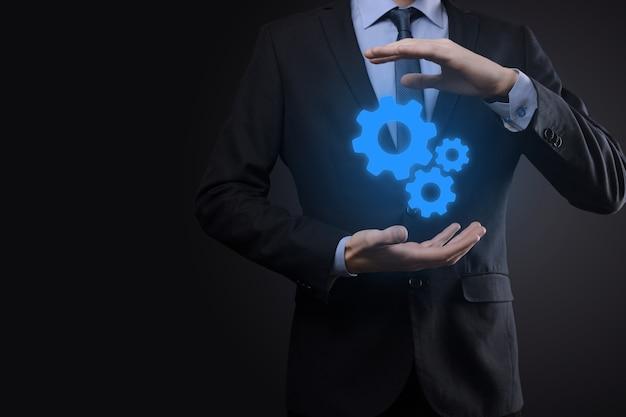 Homme d'affaires en costume tenant des engrenages métalliques et un mécanisme de roues dentées représentant le concept de travail d'équipe d'interaction, groupe de prise de main de roue d'engrenages à crémaillère virtuelle