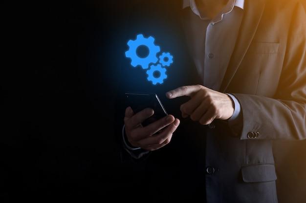 Homme d'affaires en costume tenant des engrenages métalliques et un mécanisme de roues dentées représentant le concept de travail d'équipe d'interaction, groupe de prise de main de roue à engrenages virtuels.