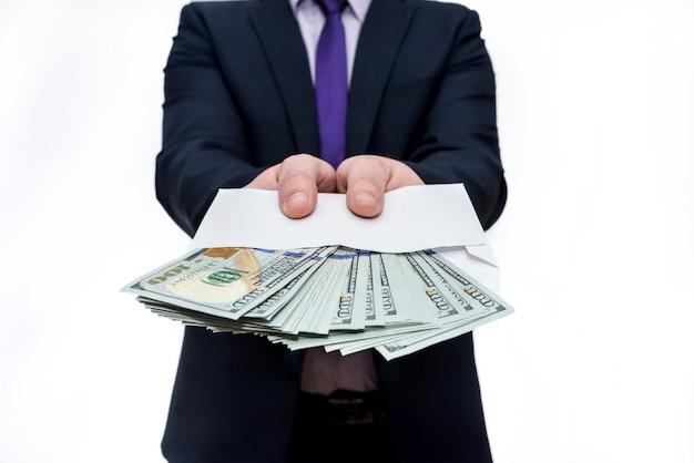 Homme d'affaires en costume tenant une enveloppe avec des billets en dollars