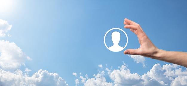Homme d'affaires en costume tenant l'icône de la main de l'utilisateur. interface d'icônes internet au premier plan. concept de média de réseau mondial, contact sur des écrans virtuels, espace de copie