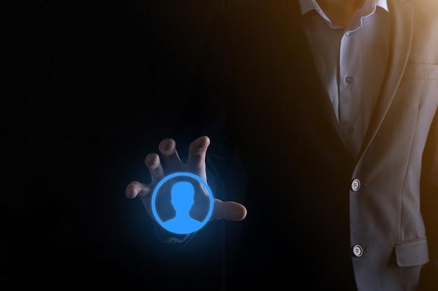 Homme d'affaires en costume tenant l'icône de la main de l'utilisateur. interface d'icônes internet au premier plan. concept de média de réseau mondial, contact sur écrans virtuels, espace de copie.