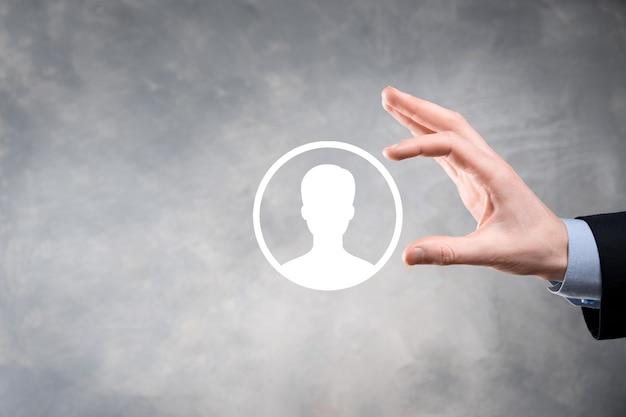 Homme d'affaires en costume tenant l'icône de la main de l'utilisateur. interface d'icônes internet au premier plan. concept de média réseau mondial, contact sur écrans virtuels, espace copie.