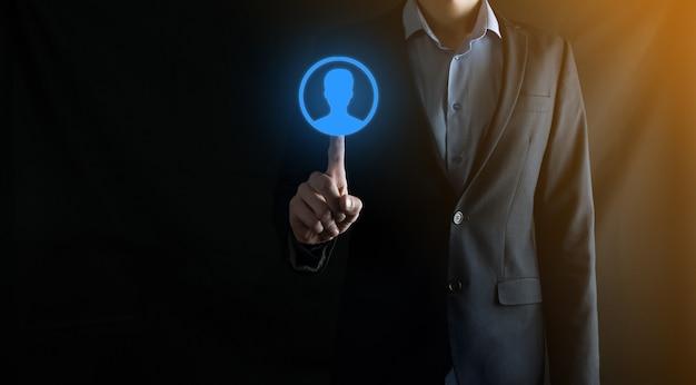 Homme d'affaires en costume tenant l'icône de la main de l'utilisateur. interface d'icônes internet au premier plan. concept de média de réseau mondial, contact sur des écrans virtuels, espace de copie.