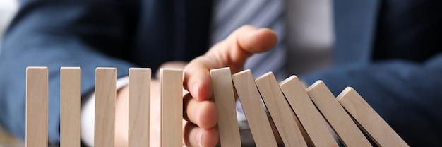 Homme d'affaires en costume tenant avec la main qui tombe séquence de gros plan de blocs de bois