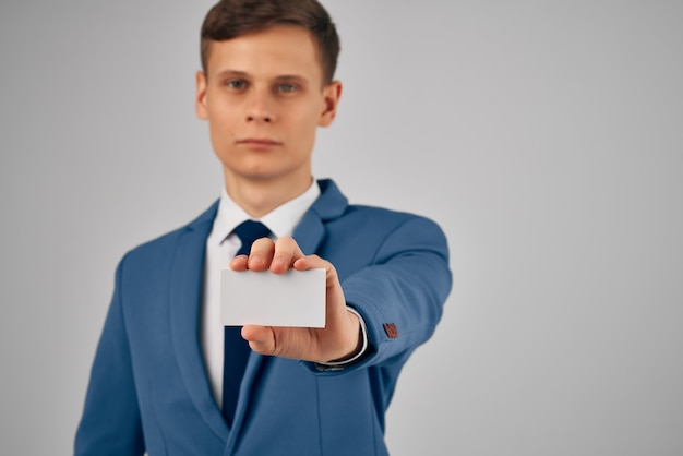 Homme d'affaires en costume tenant une publicité d'espace de copie de carte de visite