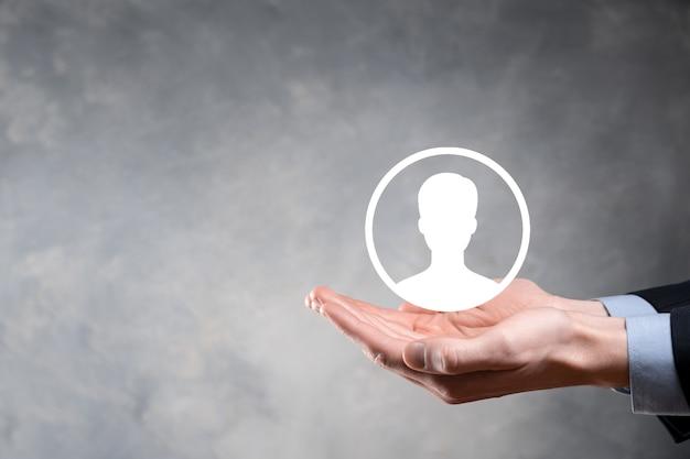 Homme d'affaires en costume tenant le symbole de la main de l'utilisateur. interface d'icônes internet au premier plan. concept de média réseau mondial, contact sur écrans virtuels, espace copie.
