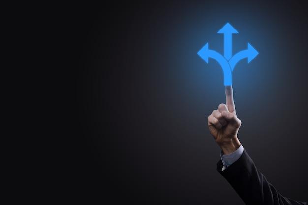 Homme d'affaires en costume tient une pancarte indiquant trois directions. dans le doute, avoir à choisir entre trois choix différents indiqués par des flèches pointant en sens inverse concept. trois façons de choisir