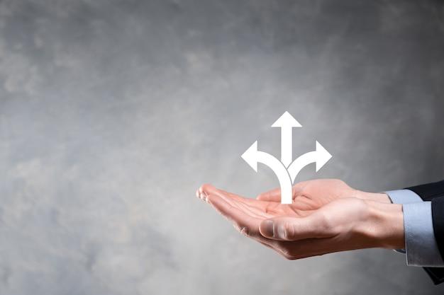 Homme d'affaires en costume tient une pancarte indiquant trois directions. dans le doute, avoir à choisir entre trois choix différents indiqués par des flèches pointant en sens inverse concept. trois façons