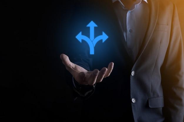 Homme d'affaires en costume tient une pancarte indiquant trois directions dans le doute devant choisir entre trois choix différents indiqués par des flèches pointant dans une direction opposée