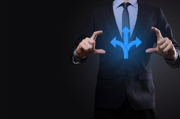Homme d'affaires en costume tient un panneau indiquant trois directions. dans le doute, avoir à choisir entre trois choix différents indiqués par des flèches pointant en sens inverse du concept. trois façons de choisir