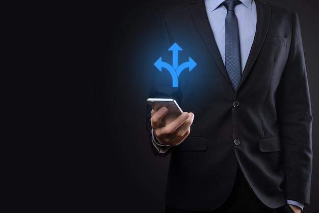 Homme d'affaires en costume tient un panneau indiquant trois directions