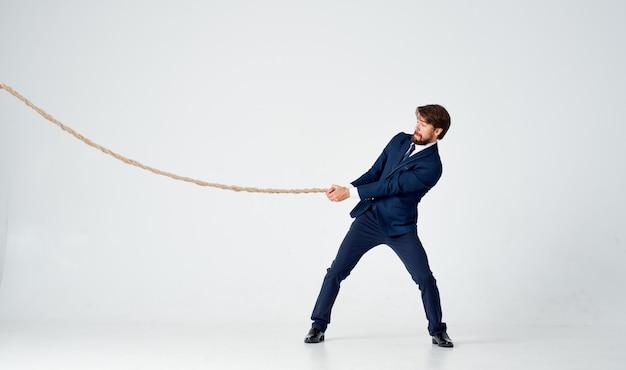Homme d'affaires en costume tire une corde sur un espace lumineux