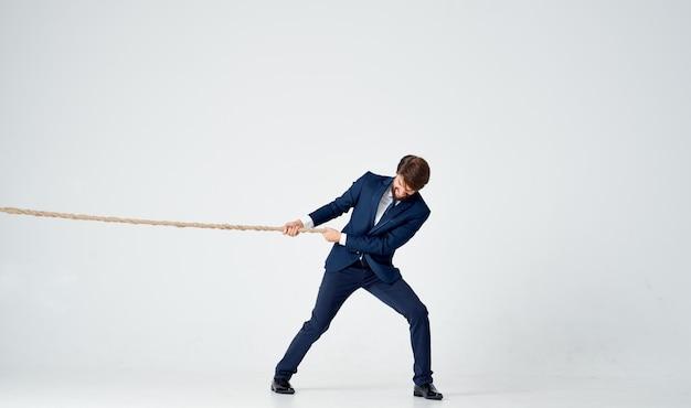 Homme d'affaires en costume tire une corde sur un fond clair