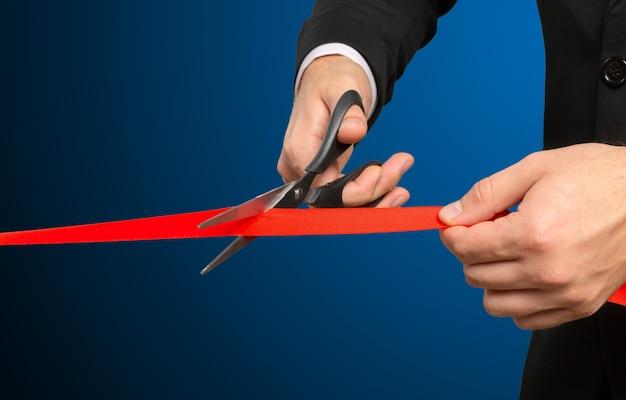 Homme d'affaires coupe le ruban rouge avec une paire de ciseaux