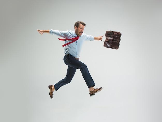 Homme d'affaires courant avec une mallette, isolé sur le mur gris du studio