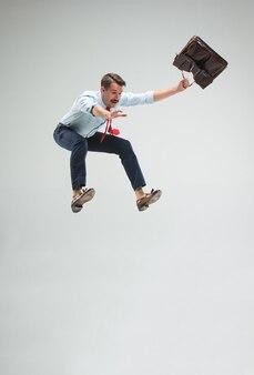 Homme d'affaires courant ou sautant avec une mallette, isolé sur le mur gris du studio
