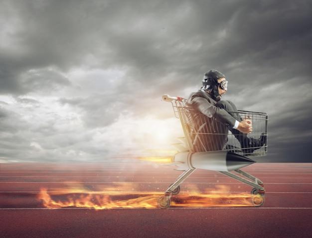 Homme d'affaires court rapidement au volant d'un chariot avec une fusée lors d'une compétition