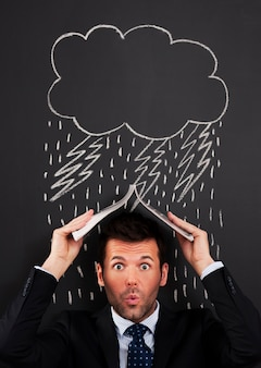 Homme d'affaires couvrant la tête de la pluie