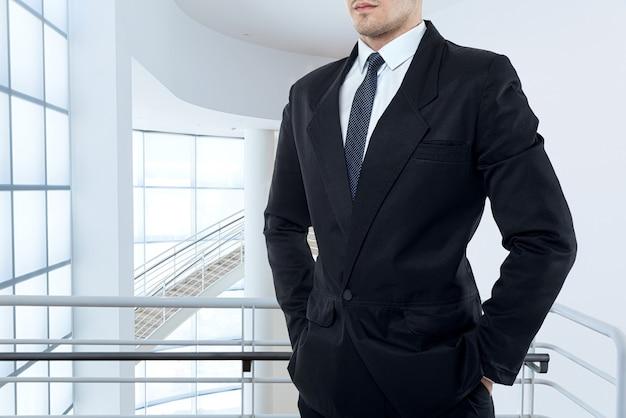 Homme d'affaires en cravate et costume noir pose dans un centre d'affaires avec des murs en verre