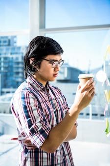Homme d'affaires créatif pensif avec café à emporter au bureau