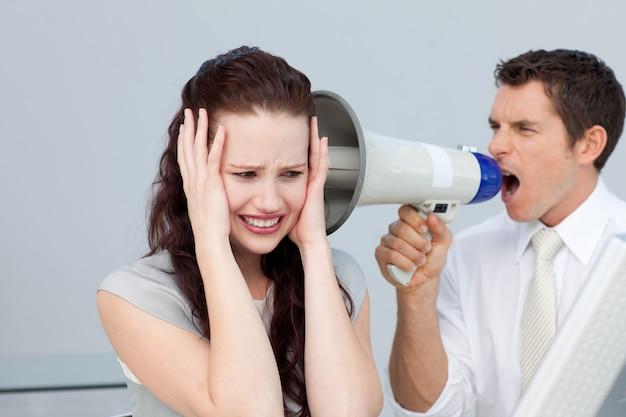 Homme d'affaires criant dans un mégaphone chez une femme d'affaires