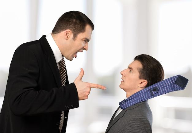 Homme d'affaires criant des ordres à un travailleur en arrière-plan