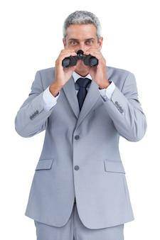 Homme d'affaires curieux observant à travers des jumelles