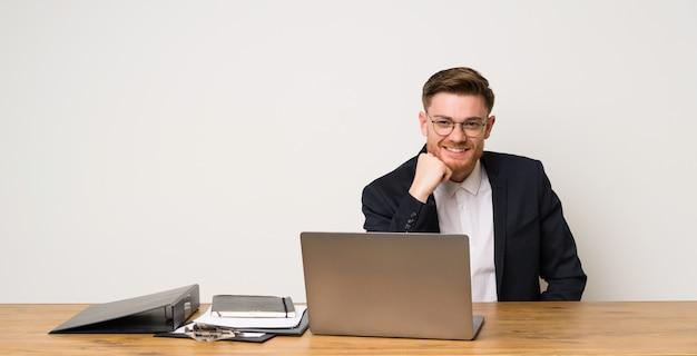 Homme d'affaires dans un bureau avec des lunettes et heureux