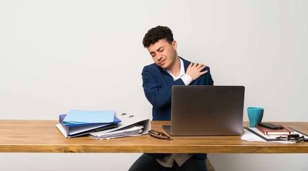 Homme d'affaires dans un bureau souffrant de douleurs à l'épaule pour avoir fait un effort