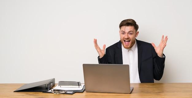 Homme d'affaires dans un bureau souriant beaucoup
