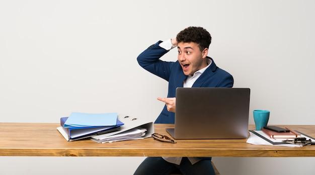 Homme d'affaires dans un bureau surpris et montrant un doigt sur le côté