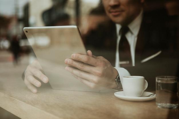 Homme d'affaires dans un café à l'aide d'une tablette
