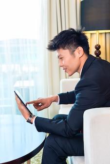 Homme d'affaires dans la chambre d'hôtel asiatique travaillant avec tablette