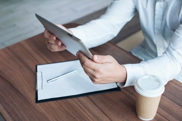 Homme d'affaires dans une chemise blanche avec une tablette numérique dans ses mains signe un contrat au bureau