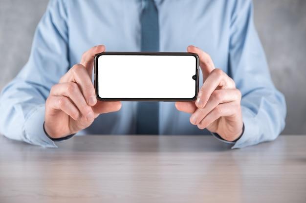 Homme d'affaires dans une chemise bleue sur le lieu de travail à la table tenant un téléphone portable, un smartphone avec un écran blanc. écran face à la caméra. maquette.concept de technologie, connexion, communication.