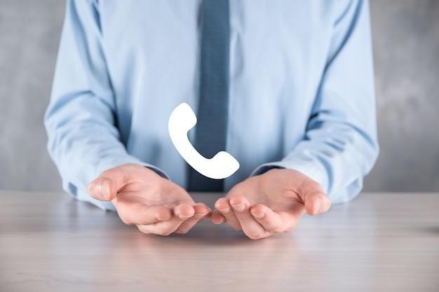 Homme d'affaires dans une chemise avec une cravate sur l'icône de téléphone de prise de mur gris. appelez maintenant business communication support center customer service technology concept.