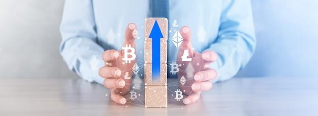 Homme d'affaires dans une chemise tient dans ses mains des cubes en bois avec une flèche, un symbole de croissance. croissance des crypto-monnaies.