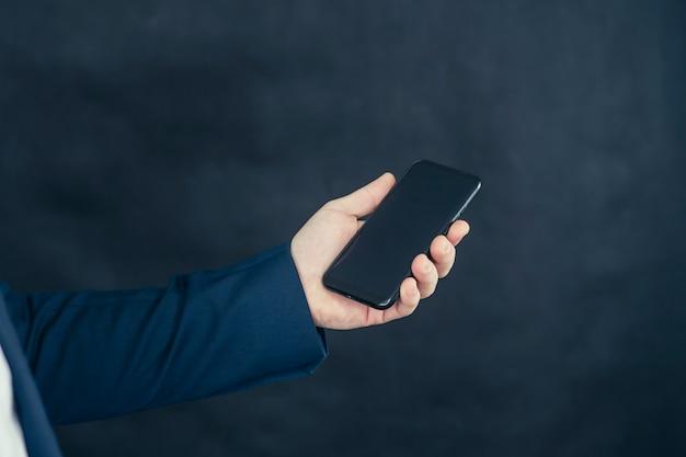 Homme d'affaires dans une chemise et une veste bleue avec smartphone à la main.