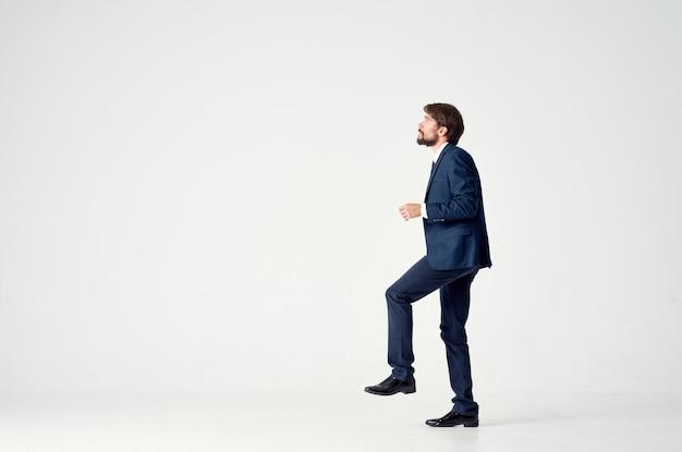 Homme d'affaires dans un costume bleu se dresse sur une jambe sur une vue latérale de fond clair