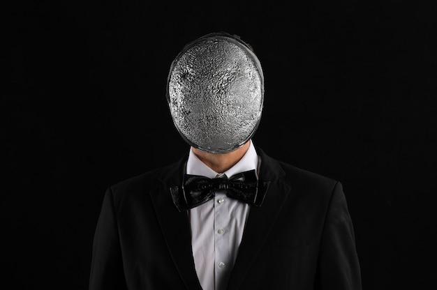 Homme d'affaires dans un masque d'argent sur fond noir
