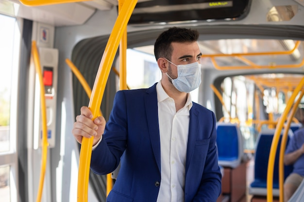 Homme d'affaires dans le métro avec masque pour éviter d'être infecté par un coronavirus
