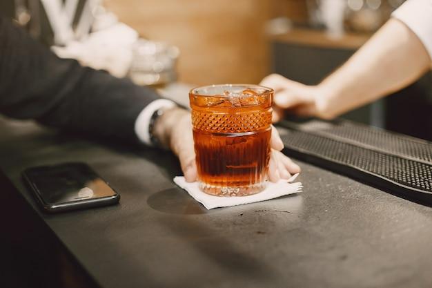 Homme d'affaires dans un pub avec cocktail